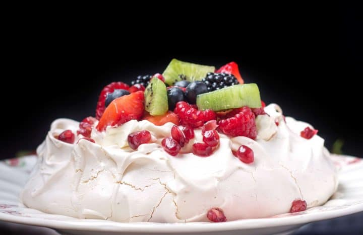 A close up of Pavlova piled high with cream and colorful fresh fruit with a second pavlova and a bowl of fruit behind it.