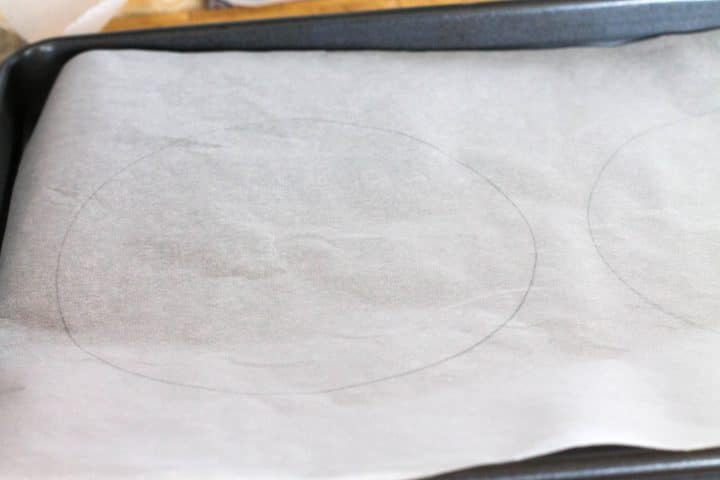 Two circles drawn on baking paper on a baking sheet