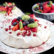 A pavlova on a dish with fresh fruit on top