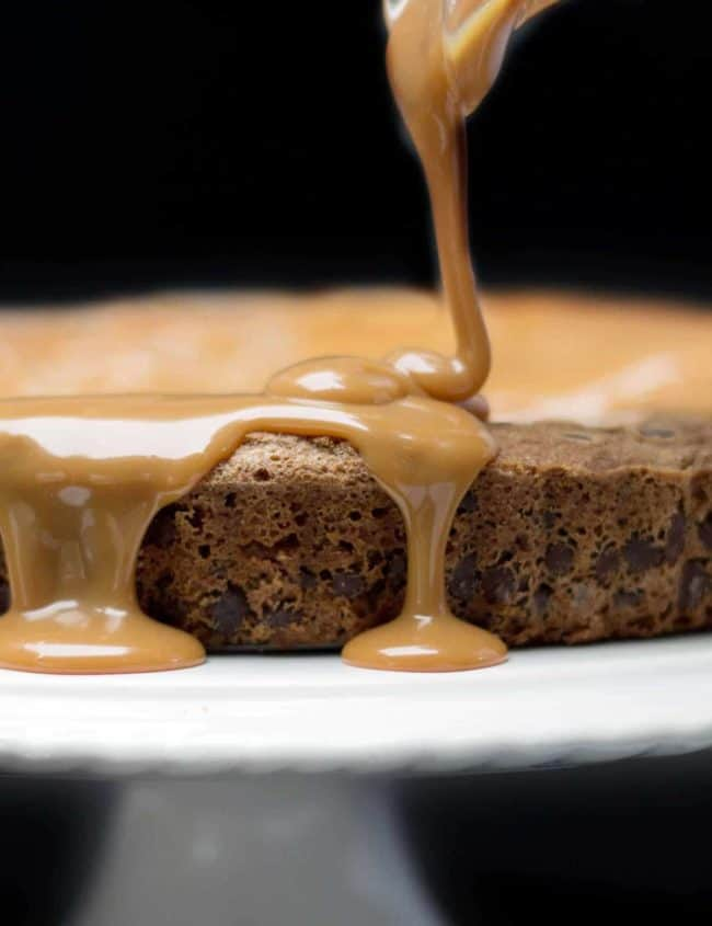 Caramel being poured onto Chocolate Chip Caramel Cake