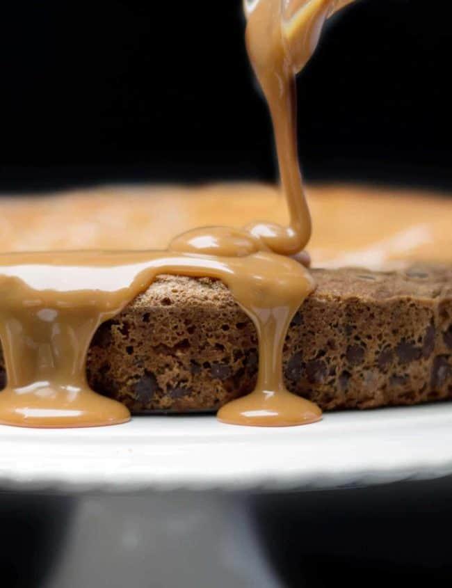 Caramel being poured onto Chocolate Chip Caramel Cake