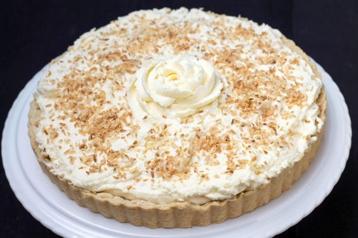 Coconut Cream Pie with a piped rose in whipped cream on top sprinkled with toasted coconut