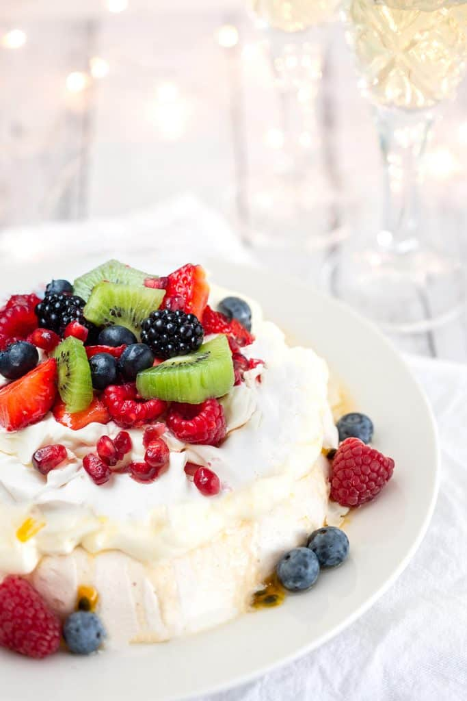Pavlova with strawberries, blueberries, raspberries and passionfruit with Christmas lights and sparkling wine in the background to celebrate the holidays in Australia