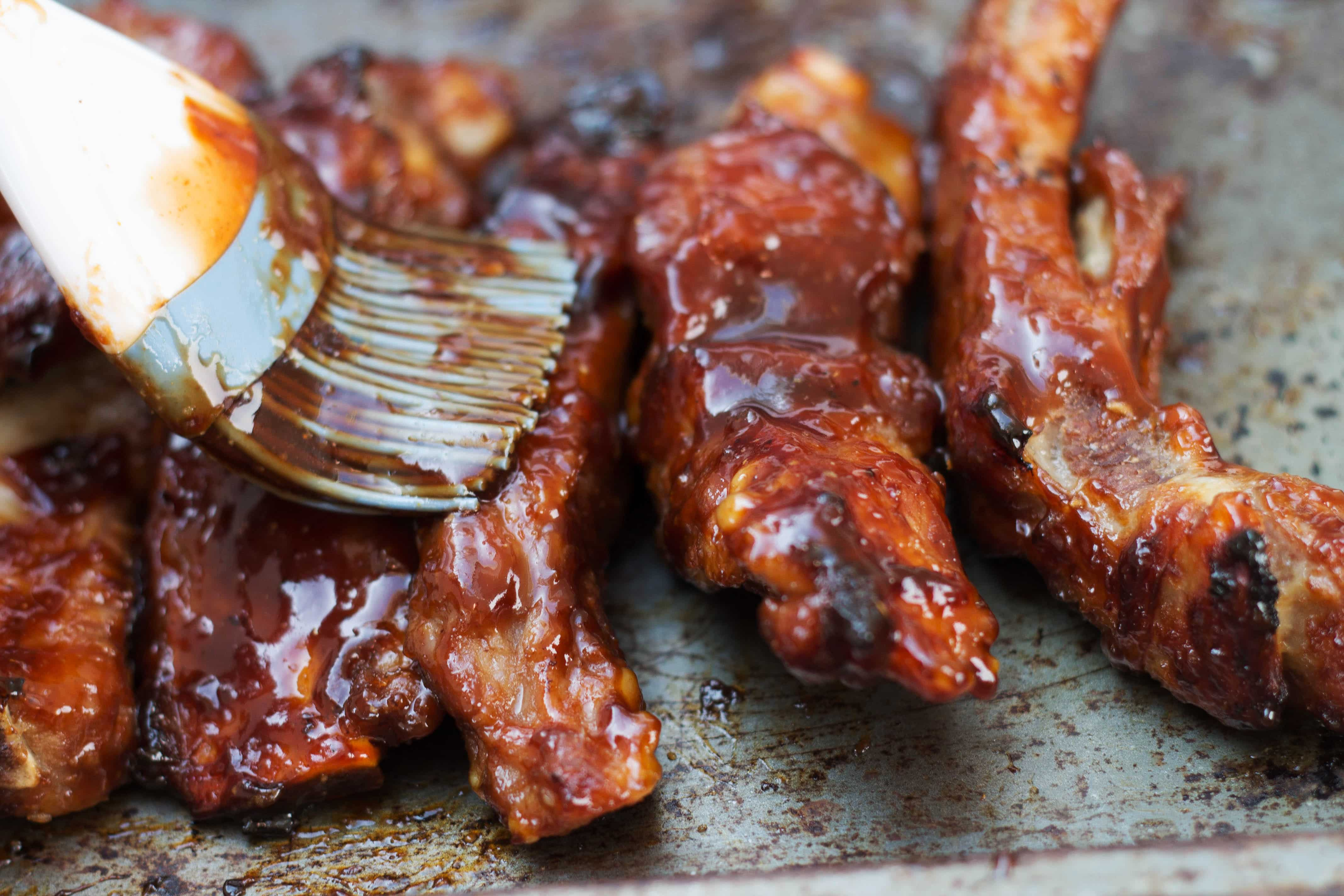 Barbecued sticky glazed ribs on a pan being brushed with sauce
