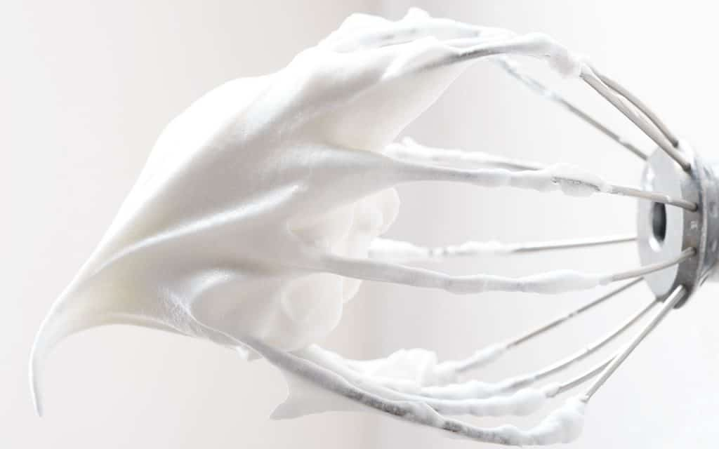 Whipped egg whites on a whisk with stiff peaks