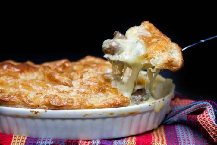 Cheesy Chicken & Mushroom Pie with a spoon scooping out a serving