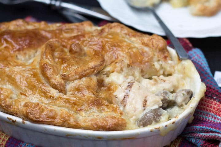 Cheesy Chicken & Mushroom Pie with a piece removed showing the filling
