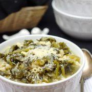 A bowl of escarole pasta soup with a spoon