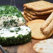 A close up of various crackers with a garlic and herb cream cheese log