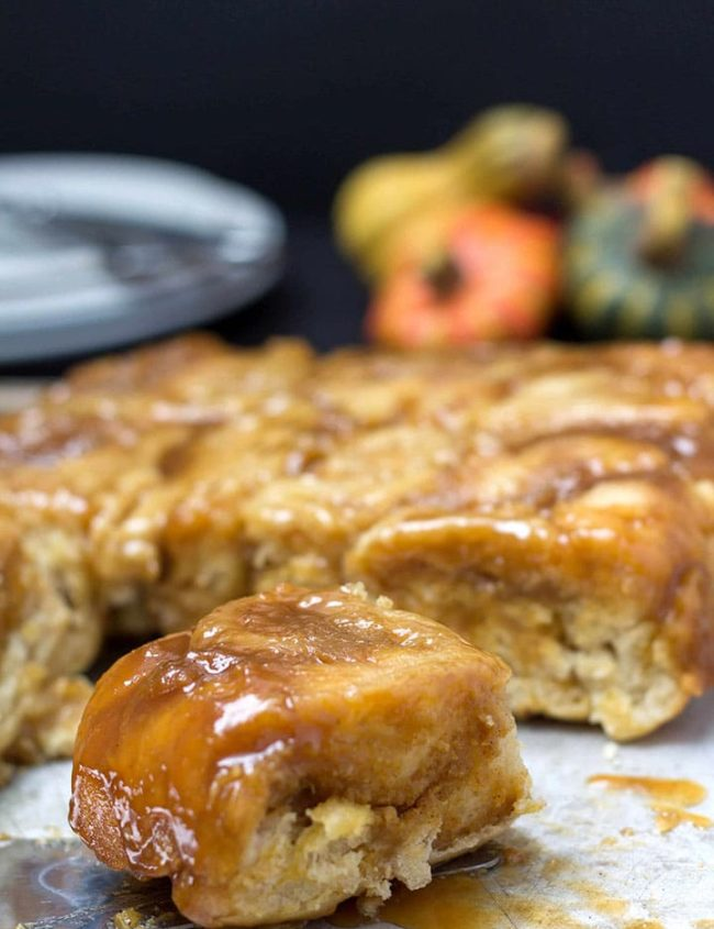 A close up of a plate of pumpkin spice sticky buns with various squash in the background