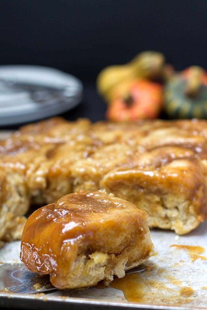 A tray of gooey pumpkin spice sticky buns with one pulled out to show the filling