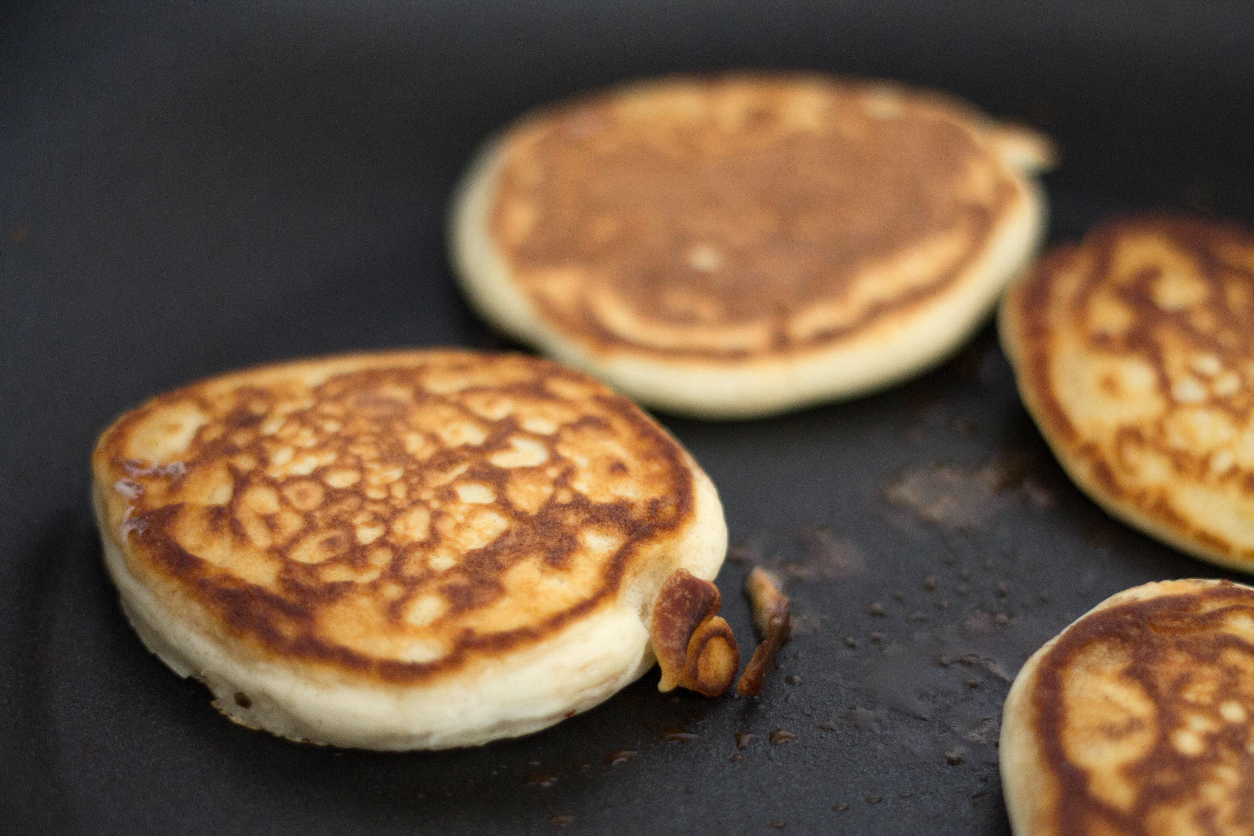 Golden brown Scotch Pancakes cooking in the pan