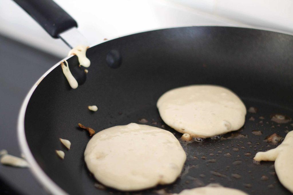 pancake batter frying in a pan