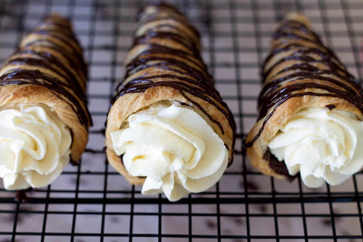 Three Dark Chocolate Cream Horns with swirled whipped cream slightly bulging out of them topped with dark chocolate drizzle.