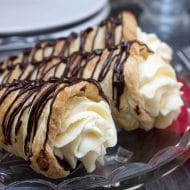 Three Dark Chocolate Cream Horns on a crystal platter with swirled whipped cream and chocolate drizzle on top