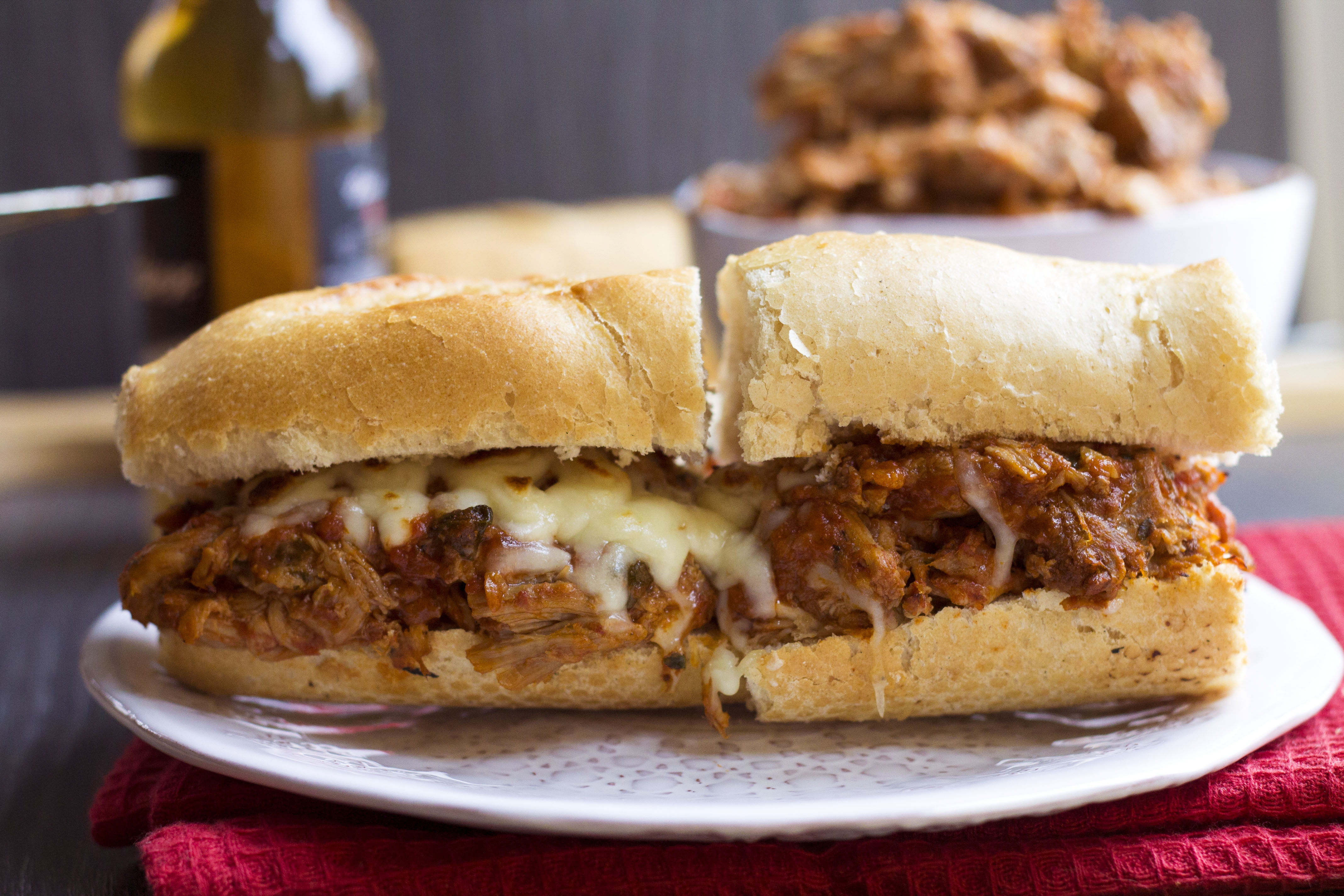 Italian pulled pork between a ciabatta roll with melted cheese oozing out.