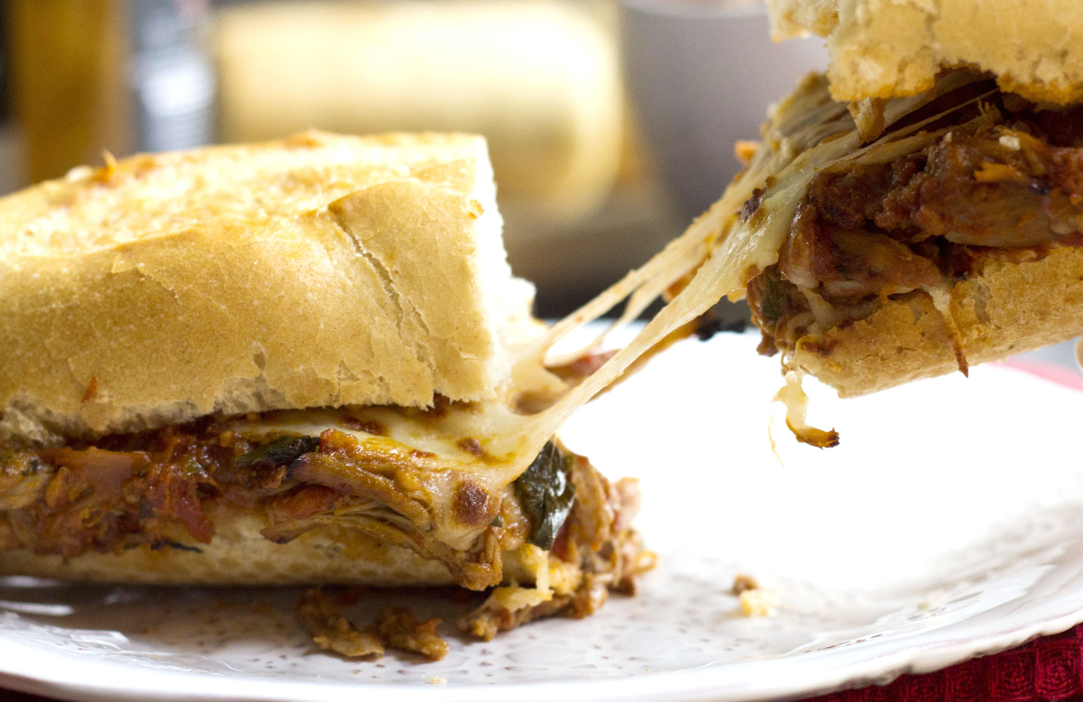 A pulled pork sandwich being pulled apart, with stringy cheese