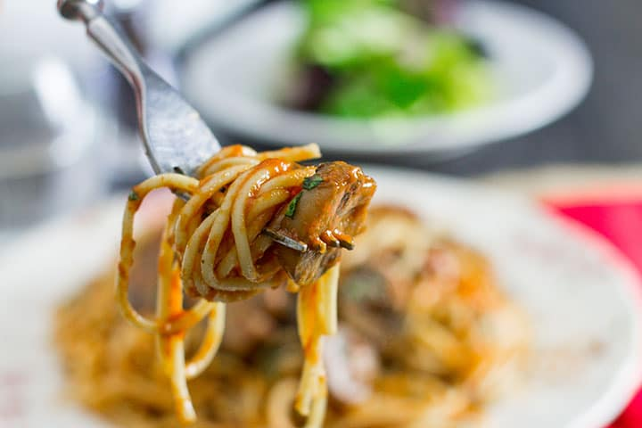 A fork with the Spaghetti With Mushroom Tomato Sauce twirlled around it and ready to eat