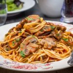 A dish piled high with Spaghetti With Mushroom Tomato Sauce