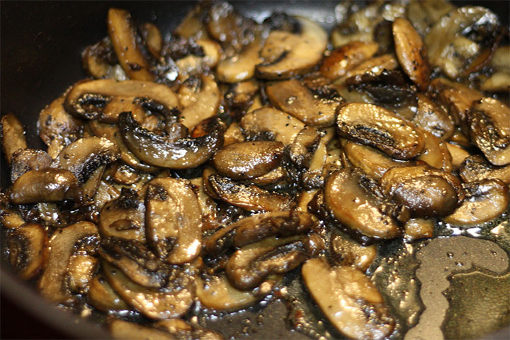 Sliced mushrooms cooked in the pan with the shallots and garlic