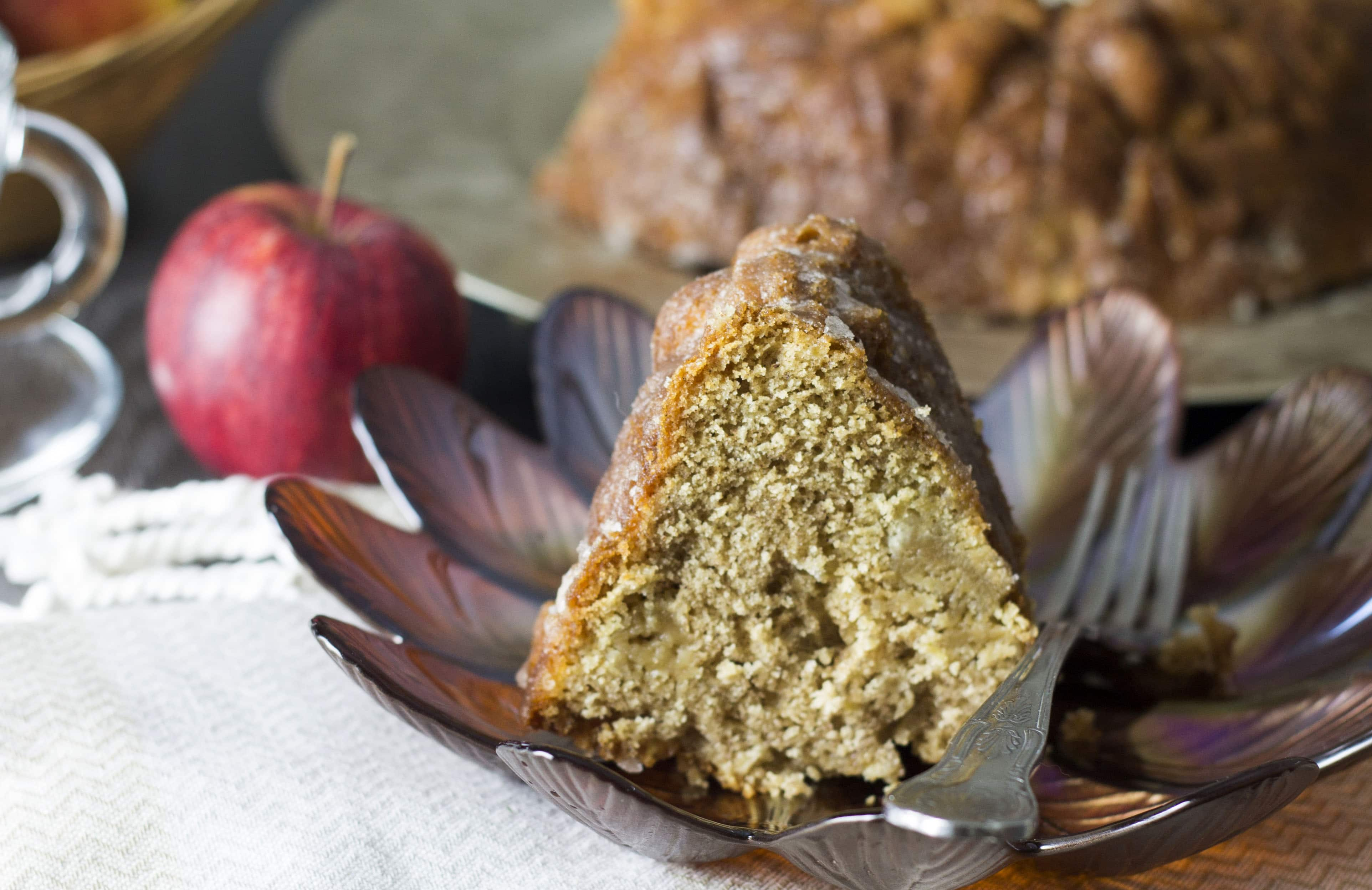 A piece of glazed apple bundt cake on a dish with an apple and the rest of the cake in the background