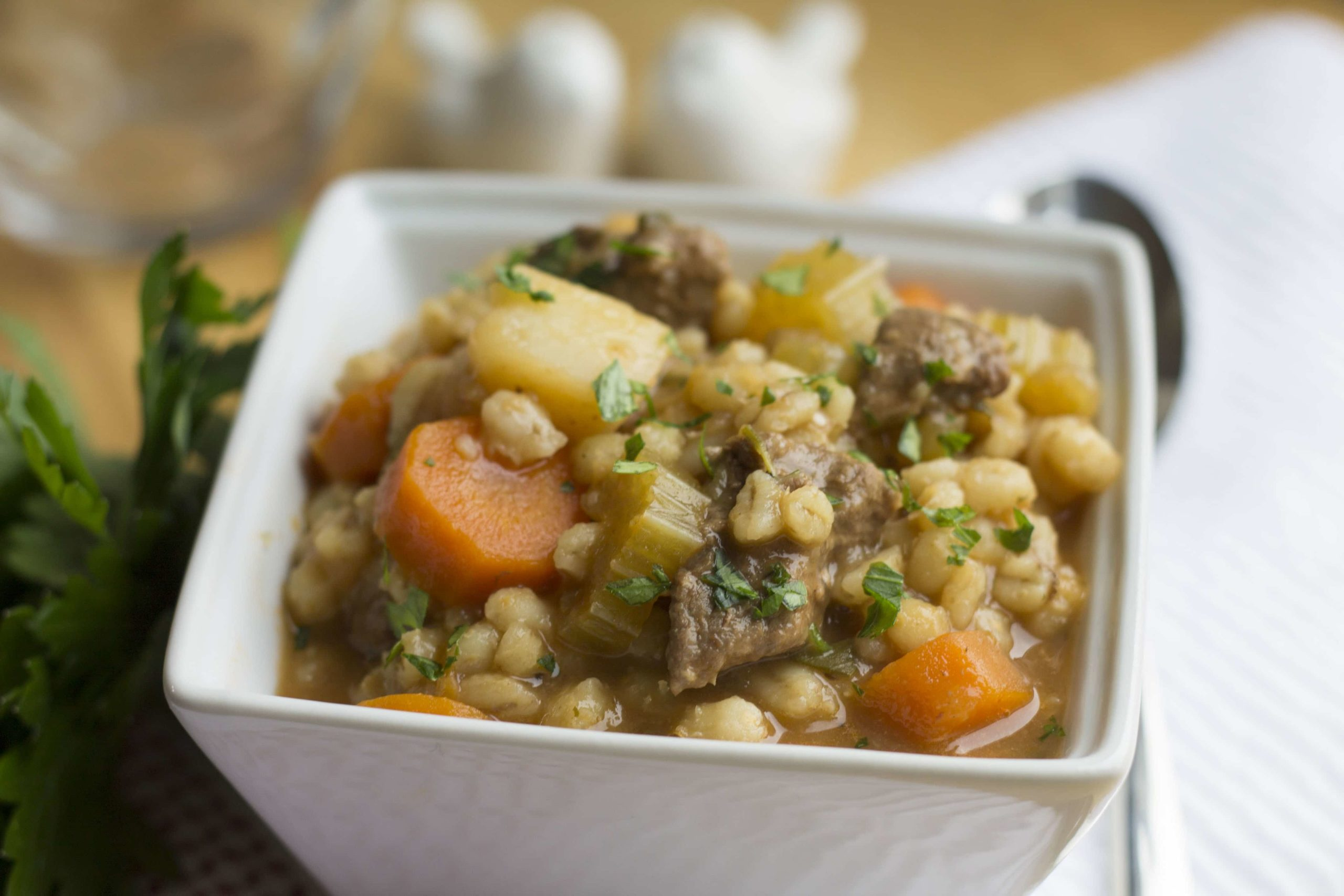Beef & Barley Soup in a white square bowl with a spoon beside