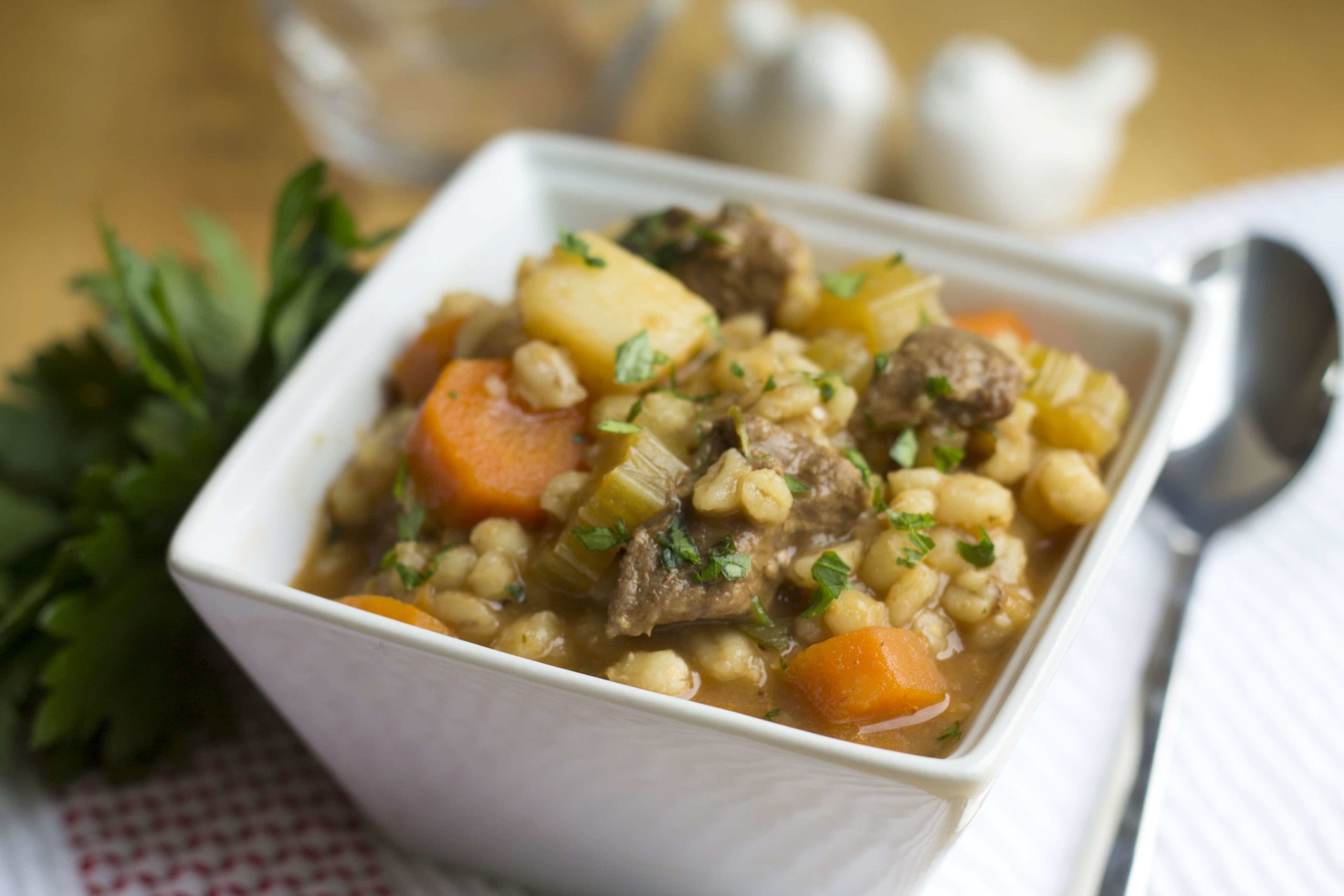 Beef & Barley Soup in a square white bowl with a spoon next to it.