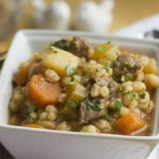 A square white bowl of beef and barley soup