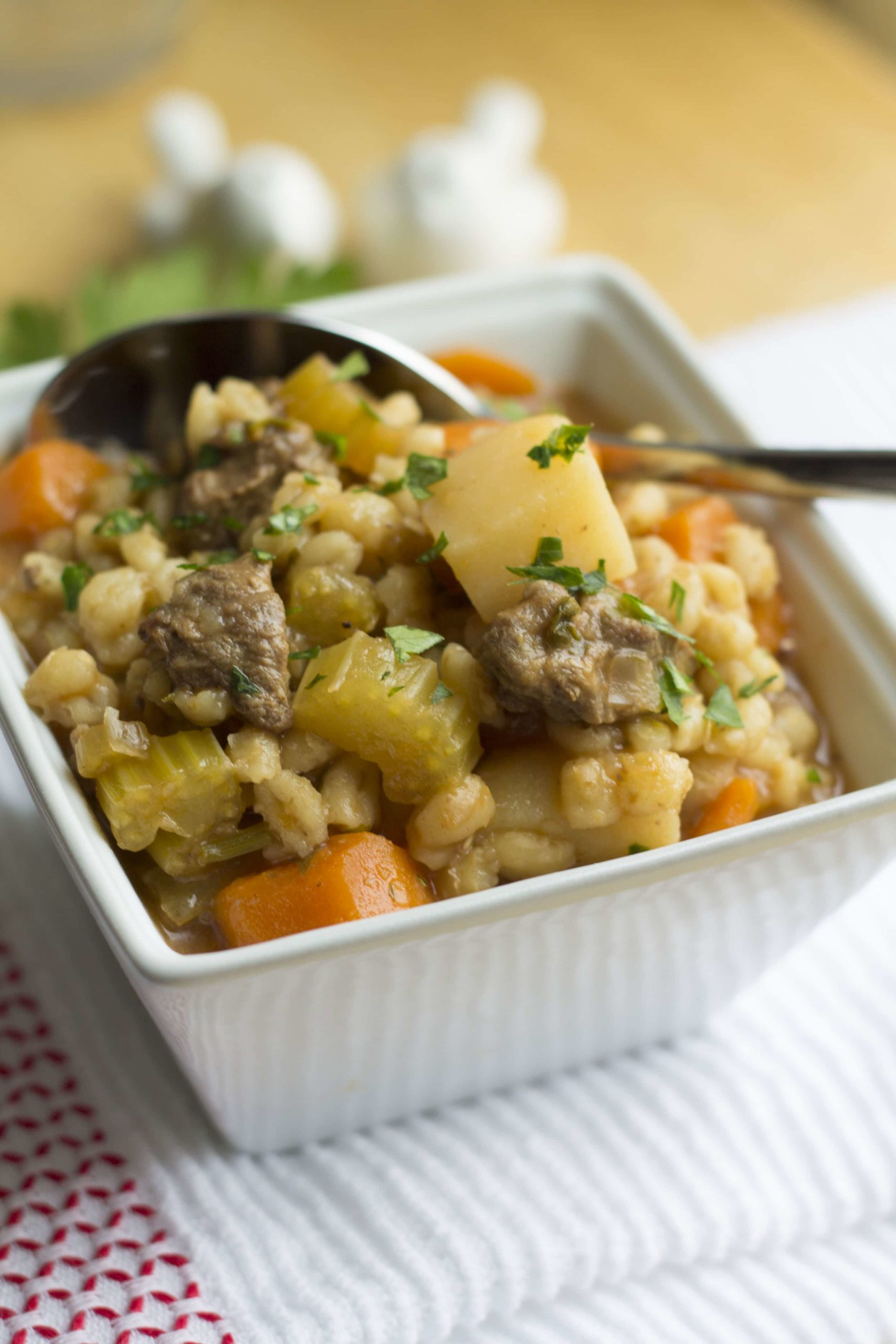 Beef & Barley Soup in a square bowl with a spoon in it