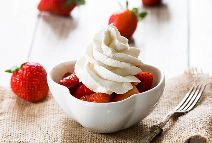 A bowl of strawberries topped with fresh whipped cream