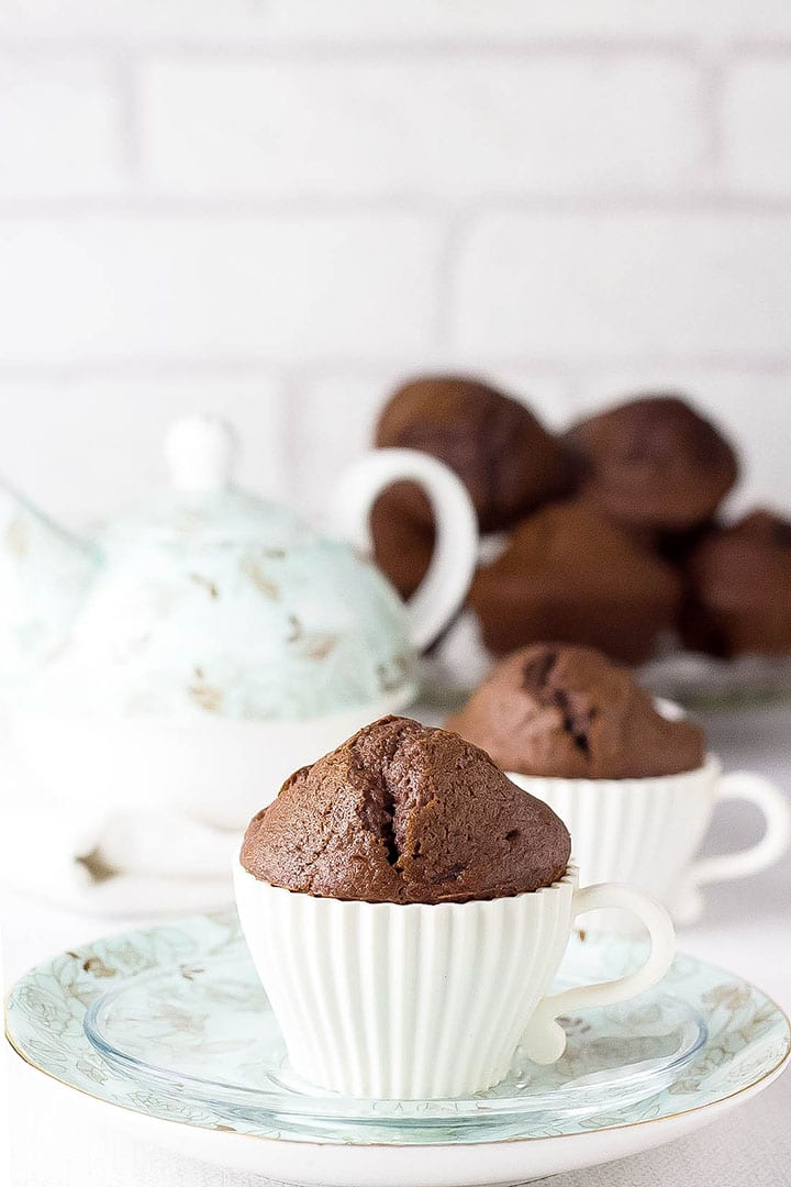 A Double Chocolate Chip Muffin in a tea cup muffin case with a teapot and more muffins in the background