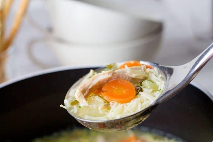 A ladle of Homemade Chicken Noodle Soup over a soup pot