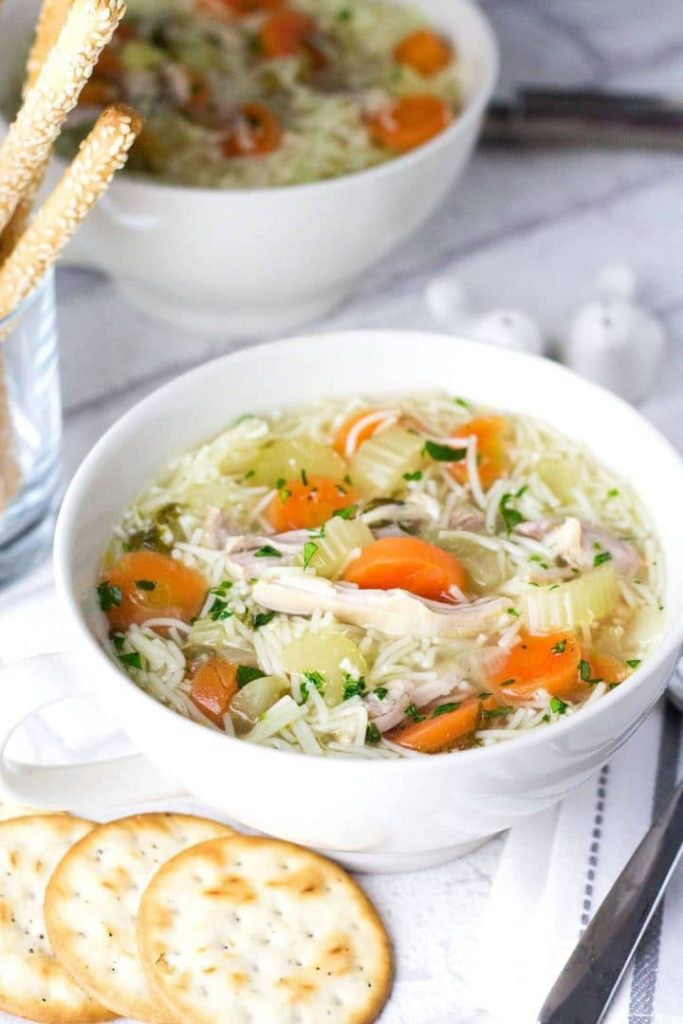 a bowl of chicken noodle soup ready to serve with crackers