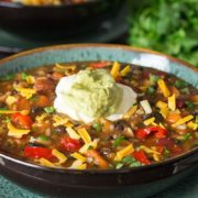 A bowl of Mexican rice and bean soup with a dollop of sour cream and guacamole on top