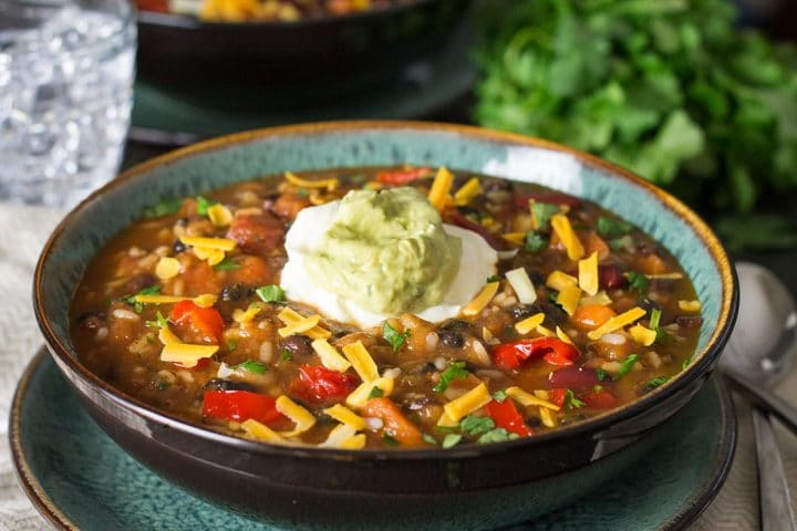 A bowl of Mexican Rice and Bean soup topped with sour cream and guacamole