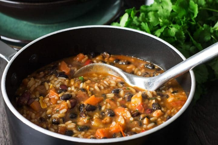 Mexican Rice & Bean Soup in a large pot with a ladle scooping the soup
