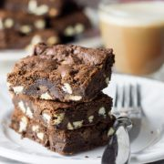 three triple chocolate chip bars on a plate with a fork and a glass mug of coffee in the background