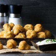 Side view of Baked Breaded Garlic Mushrooms in a black bowl served with a sour cream dip