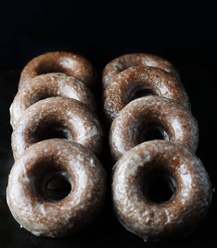 Eight chocolate glazed doughnuts in two rows laying up against each other.