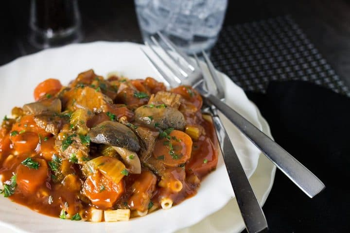 Italian Beef Stew in a white bowl served on pasta with a fork next to the plate