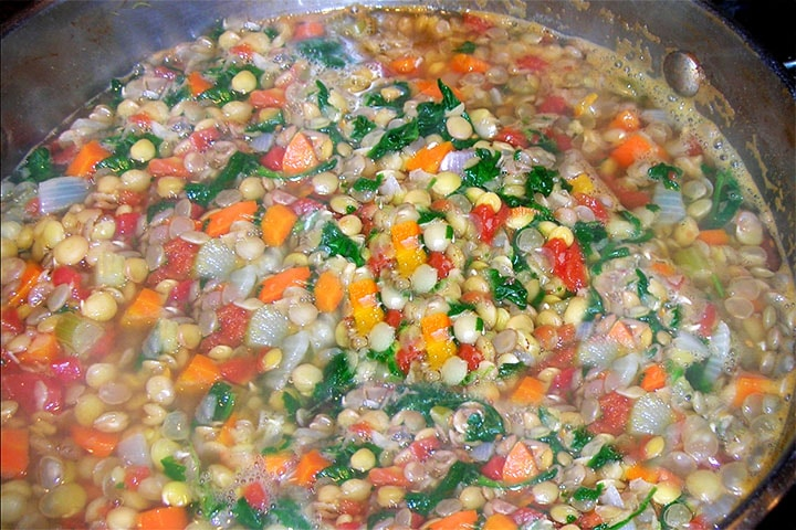 A close up of the the lentils, stock, parsley, carrots and onions before cooking down into the soup