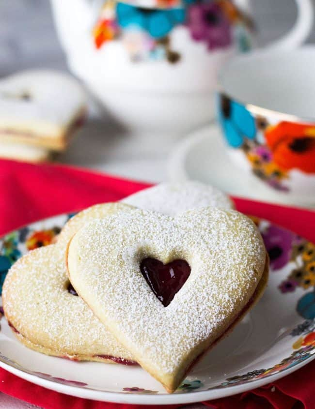 two Raspberry Butter Cookies on a plate dusted with powdered sugar
