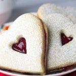 A close up of a plate of heart shaped raspberry butter cookies