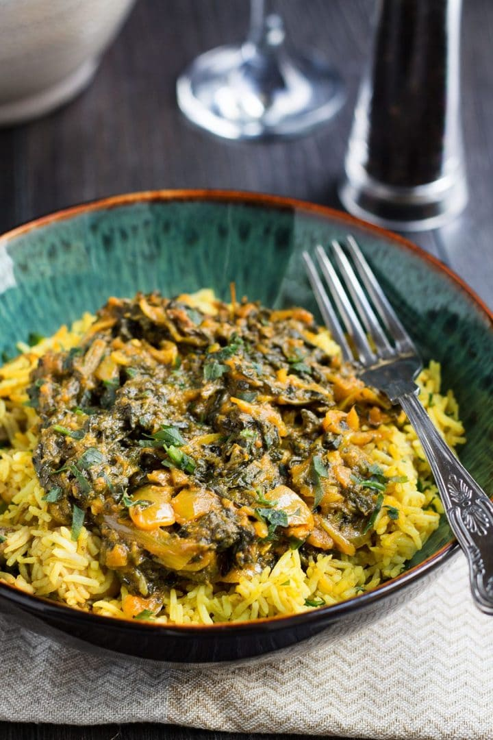Quick & Easy Sag Bahji {Spinach Curry} served in a turquoise bowl over yellow rice