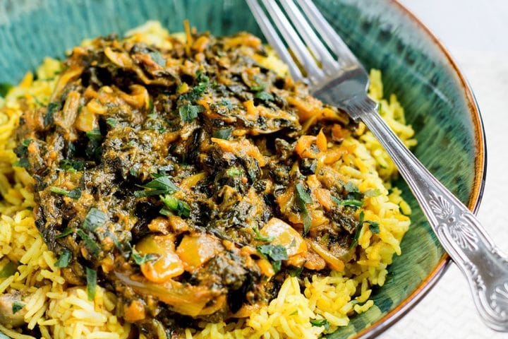 A close up of a portion of spinach curry Sag Bahji served on vibrant yellow rice