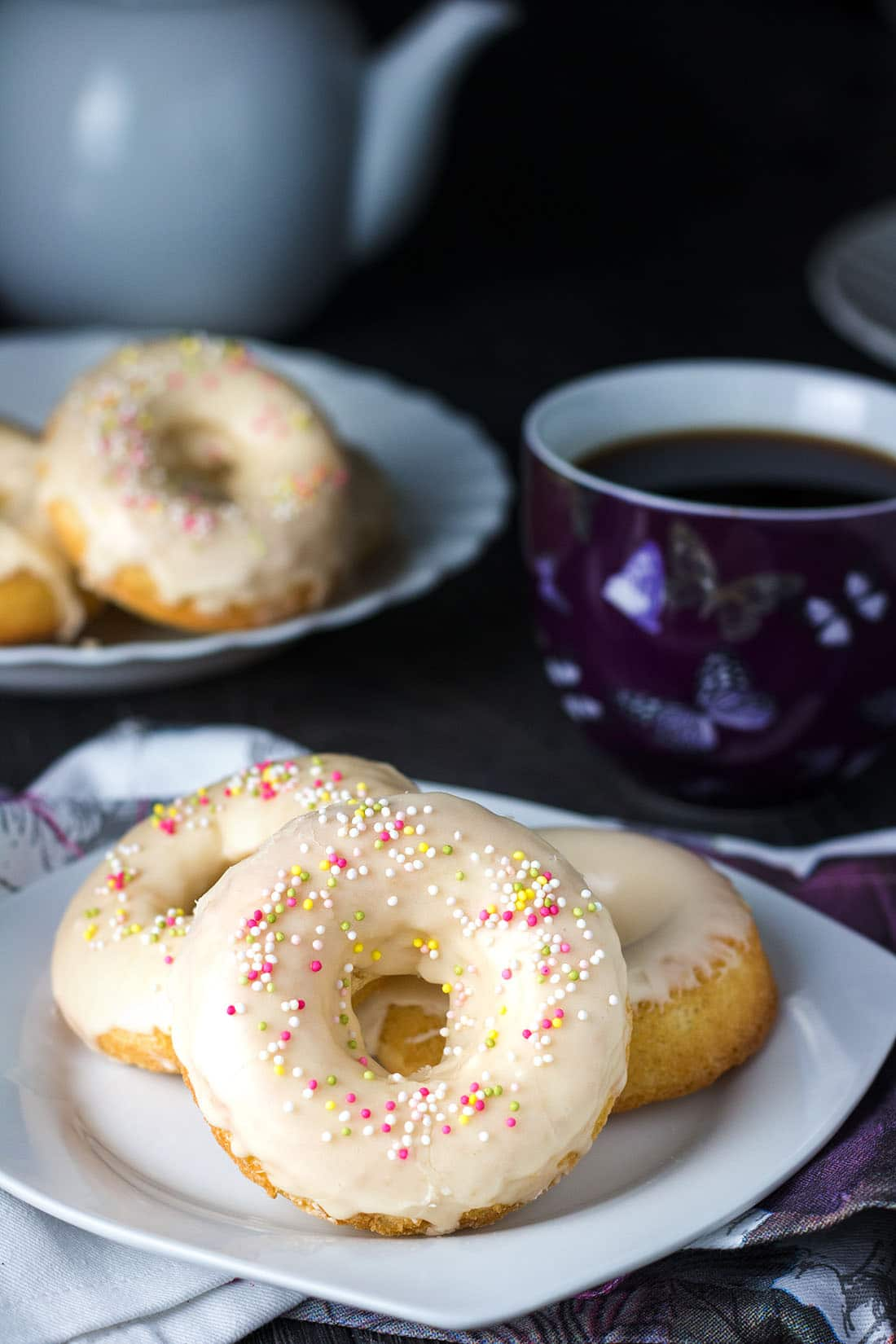 Easy Baked Iced Vanilla Doughnuts on a plate with the rest on a platter in the background an a mug full of coffee next to the plate.