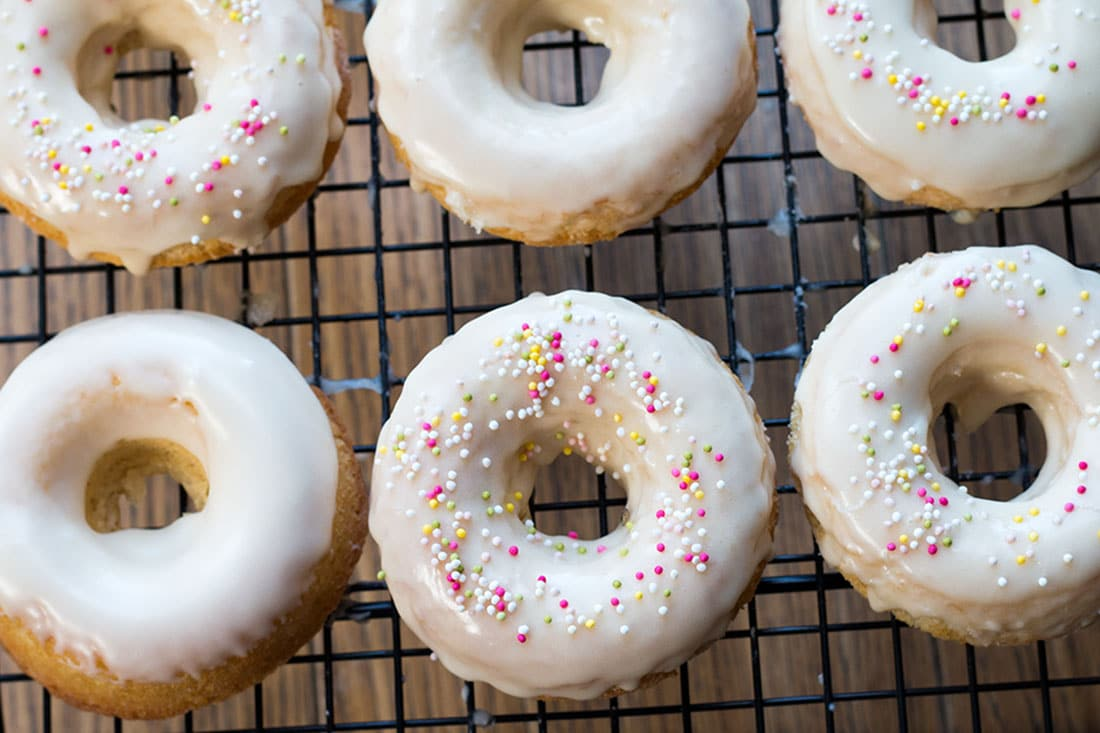 The Baked Iced Vanilla Doughnuts on a cooling rack half with sprinkles and half with just icing.