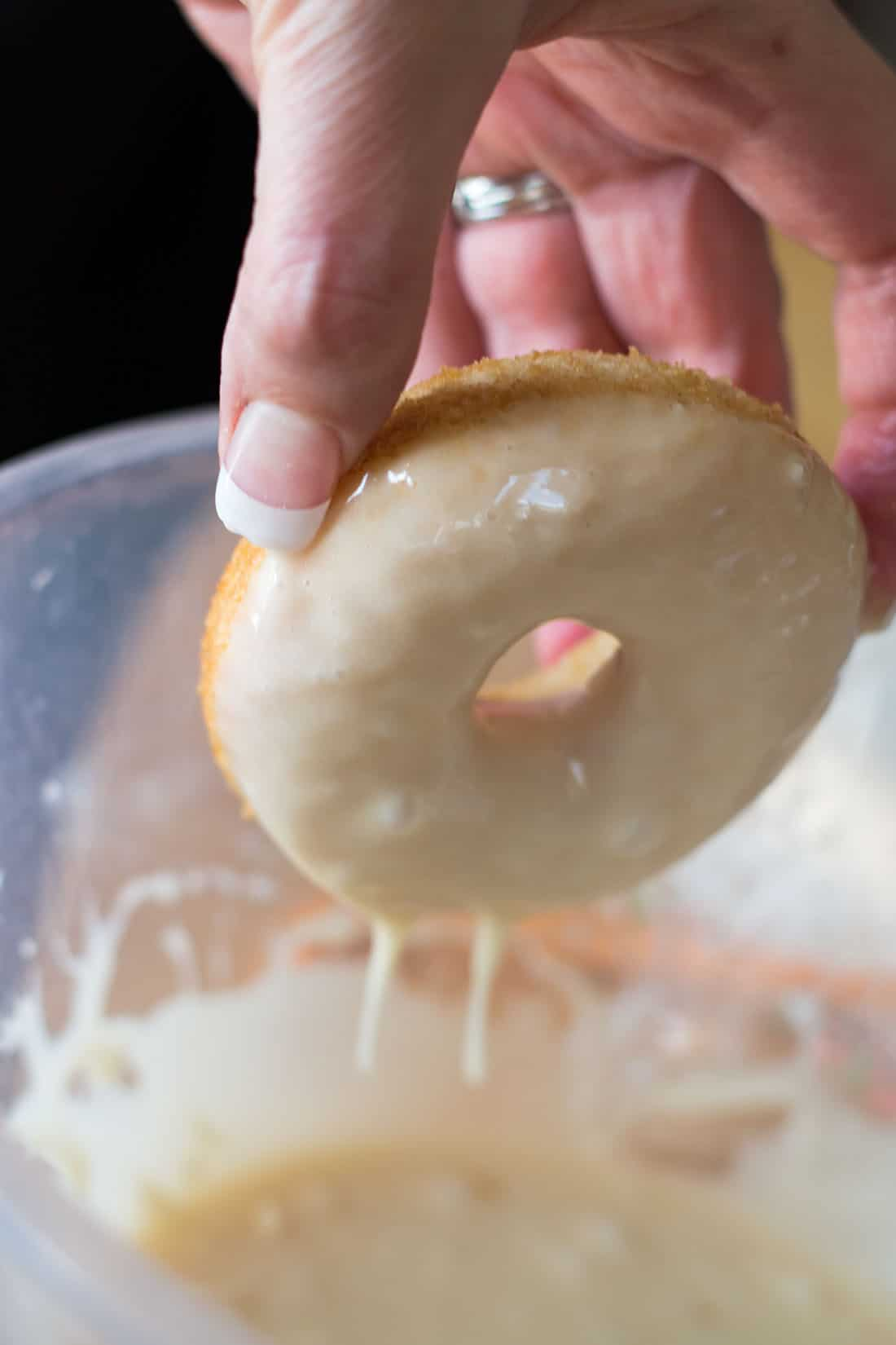 A doughnut being dipped in icing