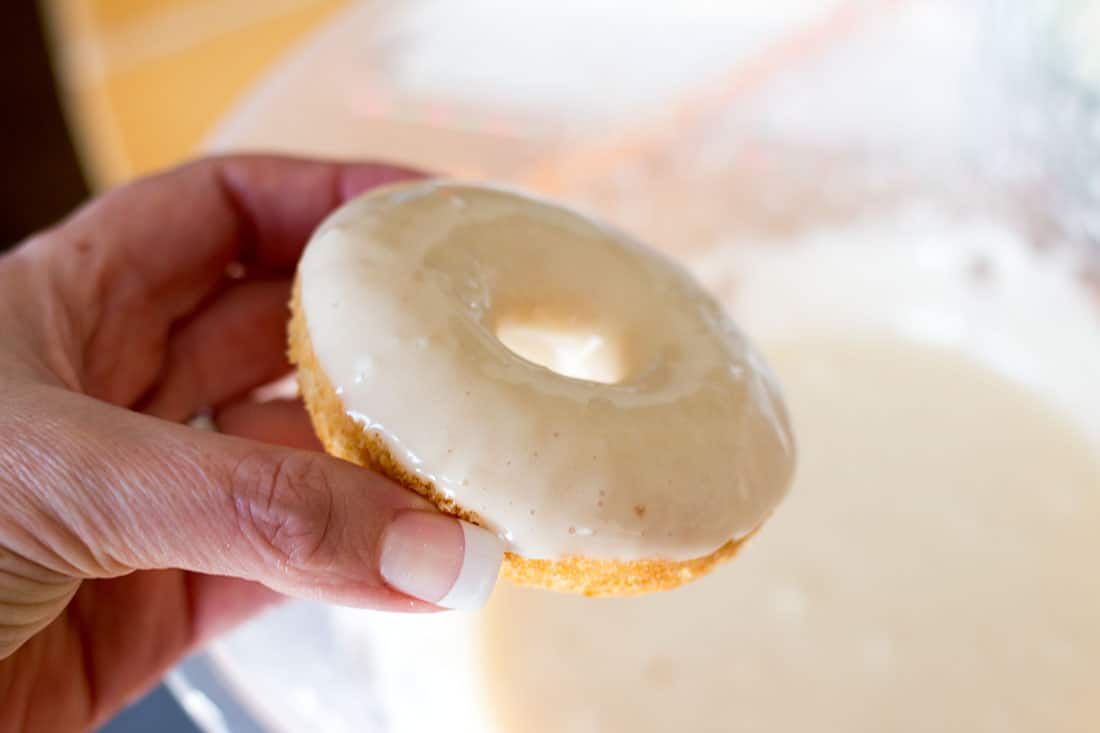 The baked vanilla doughnut wet with icing just after being dipped.