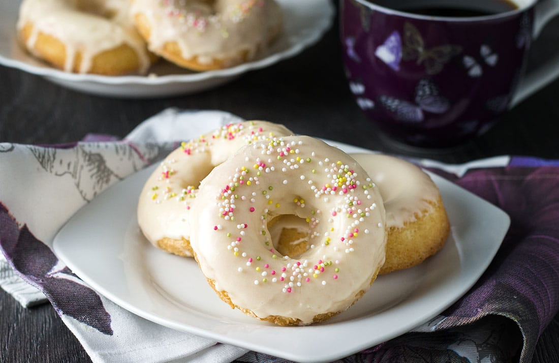 A plate with three iced vanilla doughnuts with colored sprinkles and a mug of coffee in the background.